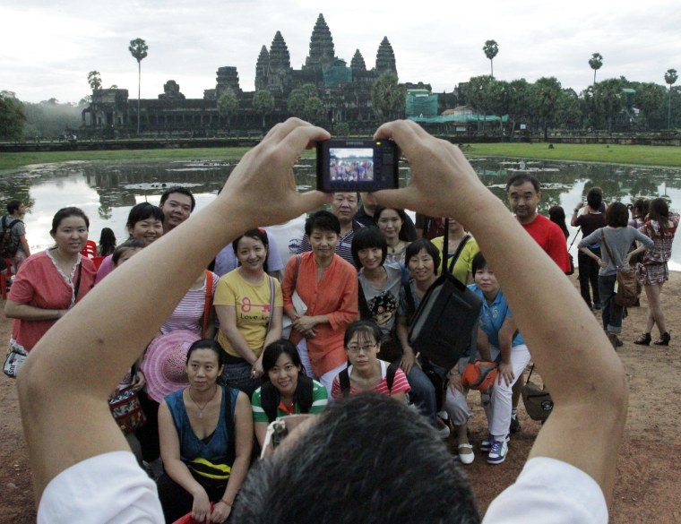 Image: Visitors pose for photographs near the Angkor Wat temple in Siem Reap