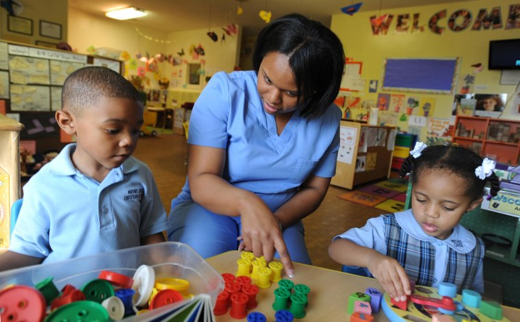 Teacher Verdavia Coleman works on fine motor skills with Ethan Vaughan, 4, and Madelyn Evans, 2, both of Jackson, at Mother Goose Christian School, in Jackson, Miss. The USDA wants daycare centers to serve healthier lunches.