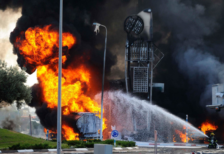 Firefighters extinguish a fire that broke out after a rocket hit a gas station in the southern Israeli city of Ashdod on July 11, 2014.