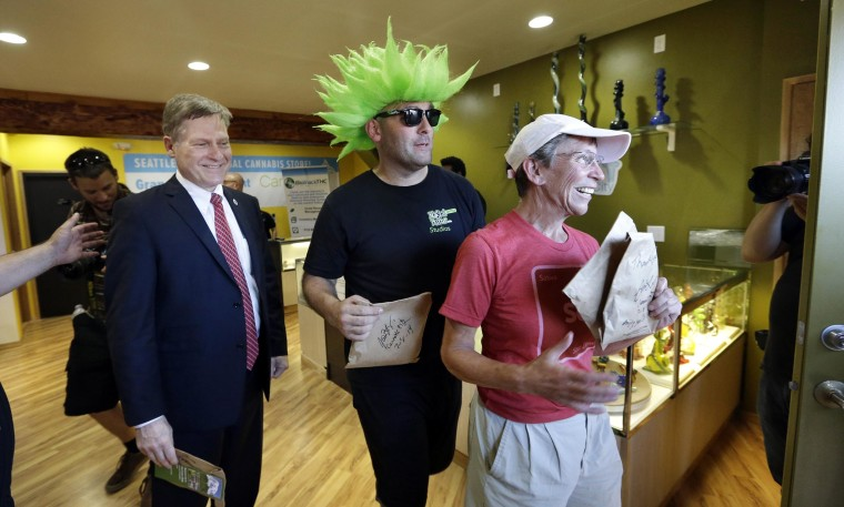Image: Seattle City Attorney Pete Holmes, left, Jeremy Cooper and Deb Greene walk out after being among the very first customers to legally purchase recreational pot in Seattle at Cannabis City, Tuesday, July 8, 2014.