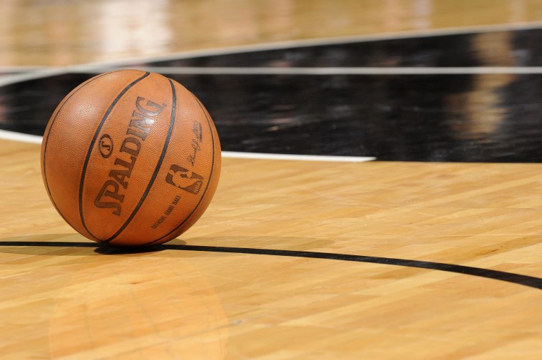 A basketball sits on a court.