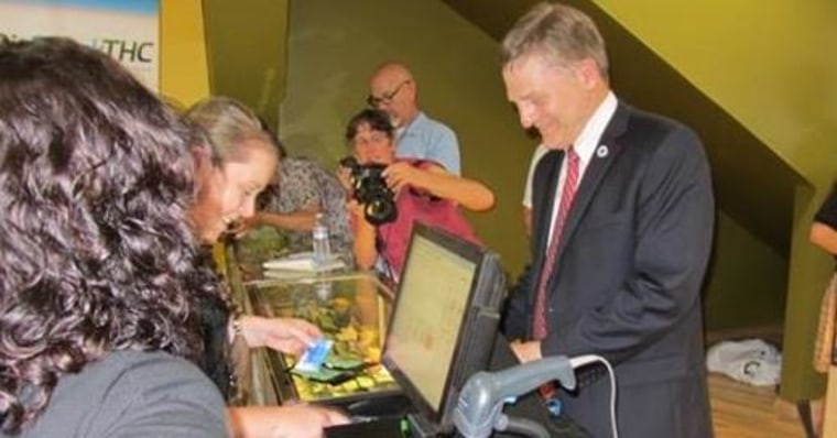 IMAGE: Seattle City Attorney Pete Holmes buying marijuana legally Tuesday at Cannabis City in Seattle.