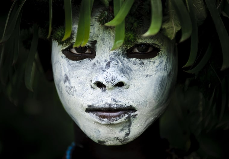 Image: Face of a young boy painted with clay and crowned with green leaves