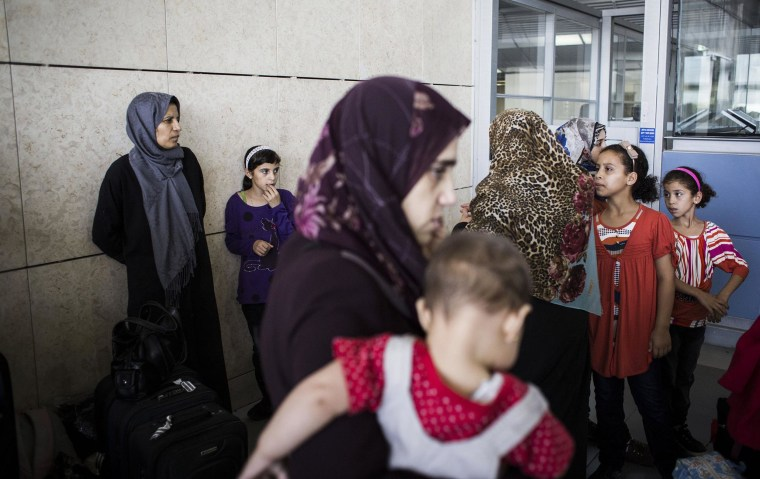 Image: Gaza residents with dual nationality passports gather at the Erez crossing