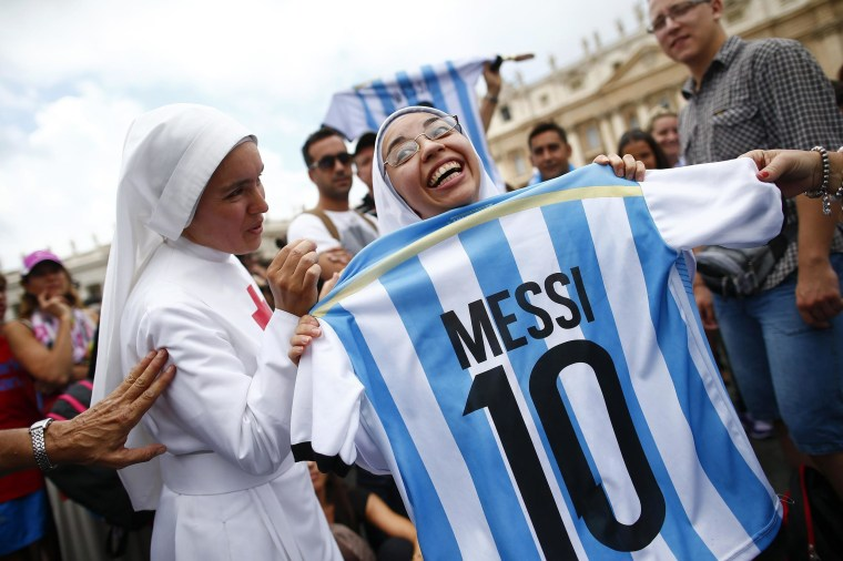 Image: A nun holds an Argentinian national soccer team jersey as she waits for Pope Francis' Sunday Angelus prayer in Saint Peter's square at the Vatican