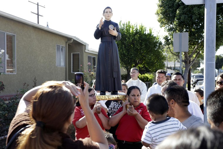 Image: Members of St. Marcellinus parish carry relic of Saint Toribio Romo Gonzalez, saint of immigrants and border crossers, during procession on first day of Southern California tour of the relic in Commerce