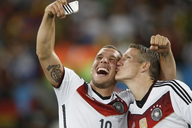 Image: Germany's midfielder Bastian Schweinsteiger and Germany's forward Lukas Podolski take a 'selfie' after their victory