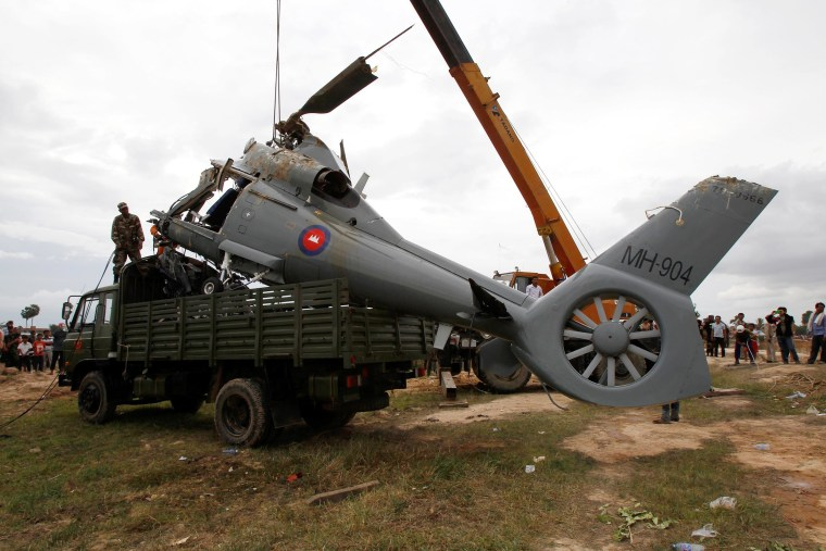 Image: Soldiers load an aft section of a helicopter retrieved from a pond following its crash in Prey Sar village at the outskirt of Phnom Penh, Cambodia