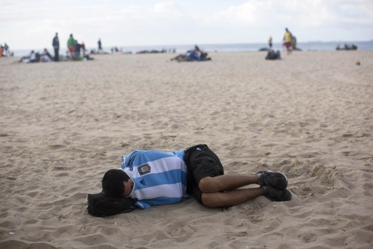 An Argentina soccer fan sleeps on Copacabana beach the morning after his team was defeated by Germany at the World Cup final.