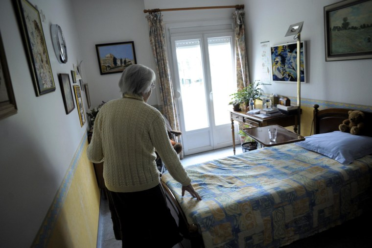A woman, suffering from Alzheimer's desease, walks in her room on  in a retirement house in Angervilliers, eastern France.