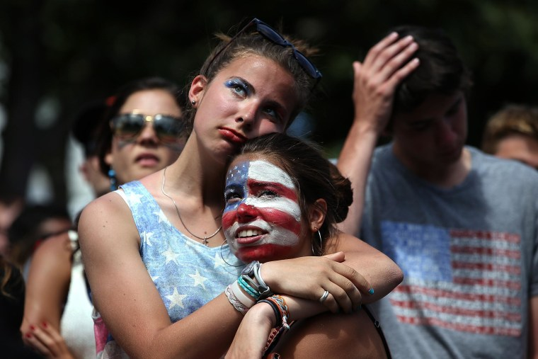 Image: Soccer fans Sofia Trogu and Anita Wray embrace as they watch the final minutes of a live simulcast of the FIFA World Cup quarter final match between USA and Belgium at the Civic Center plaza on July 1, in San Francisco, Calif.