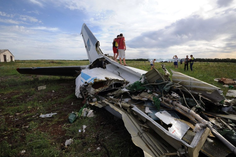 Image: People standing on the wreckage of a Ukrainian AN-26 military transport plane