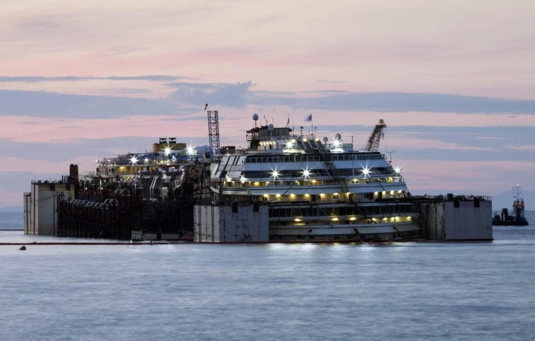 The ill-fated Costa Concordia cruise liner is illuminated by its own on-board lighting system at dawn on July 15 on the second day of the re-floating operation off the island of Giglio.