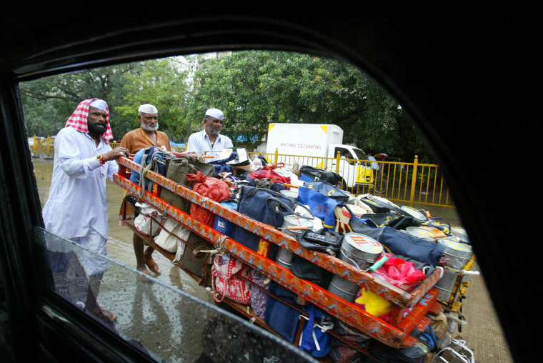 Image: Dabbawalas, or tiffin carriers, push a cart loaded with lunch boxes in the rain, as seen from inside a car, in Bombay, India, on Aug. 11, 2006.