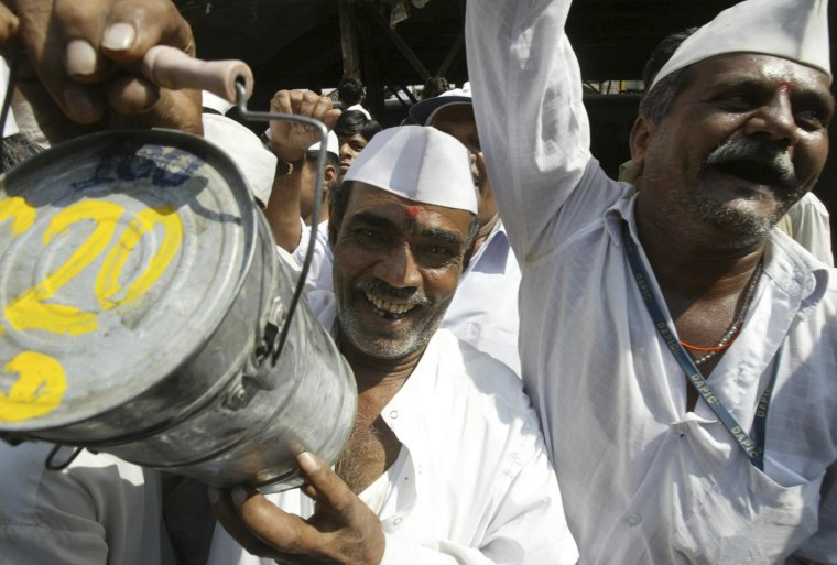 Image: A lunch delivery man or 'Dabbawala' holds up a tiffin box as he participates in a session of 'Laughter' yoga in Mumbai, India, on Feb. 22, 2008.