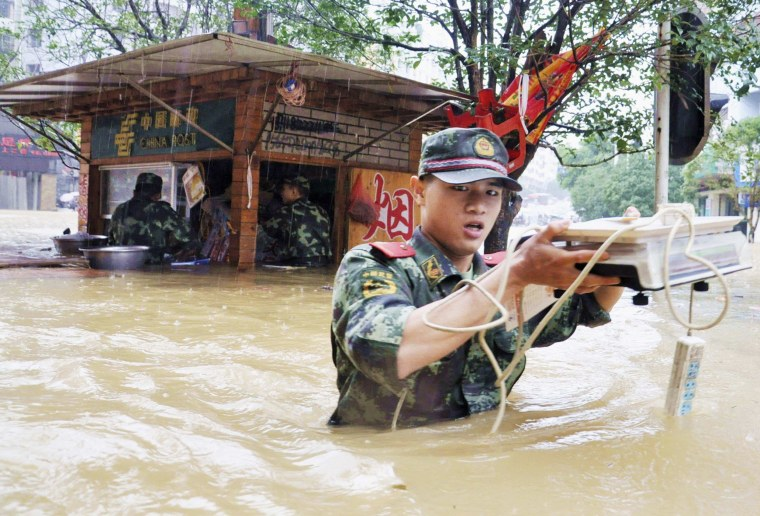 Image: A paramilitary policeman walks among floodwater as he transports residents' belongings to safety amid heavy rainfalls in Tongren