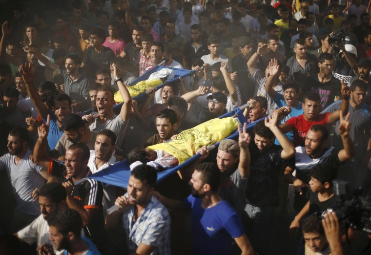 ATTENTION EDITORS - VISUAL COVERAGE OF SCENES OF INJURY OR DEATH Palestinians carry the bodies of two boys from the Baker family, whom medics said were killed with other two children from the same family by a shell fired by an Israeli naval gunboat, during their funeral in Gaza City July 16, 2014. Four Palestinian children were killed and one was critically wounded on a Gaza beach on Wednesday by the shell fired by the Israeli naval gunboat, a Palestinian health official said. Asked about the incident, an Israeli military spokesman in Tel Aviv said he was checking the report. Gaza health officials said 207 Palestinians, most of them civilians, had been killed in air and naval barrages, in the worst flareup of Israeli-Palestinian violence in two years. One Israeli has been killed by shelling from Gaza that has made a race to shelter a daily routine for hundreds of thousands in Israel.  REUTERS/Mohammed Salem (GAZA - Tags: POLITICS CIVIL UNREST TPX IMAGES OF THE DAY MARITIME MILITARY)  TEMPLATE OUT