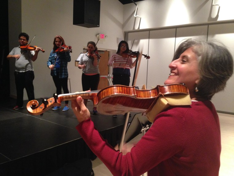 Image: Dinorah Marquez, director of the Latino Arts String Program at the United Community Center in Milwaukee, Wisconsin, with some of her students.