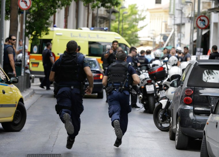 Image: Policemen run to the scene where Nikos Maziotis was arrested after a shootout