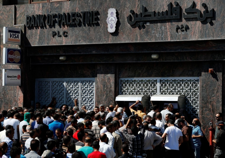 Image: Palestinians gather to withdraw money from ATM machines in Gaza City