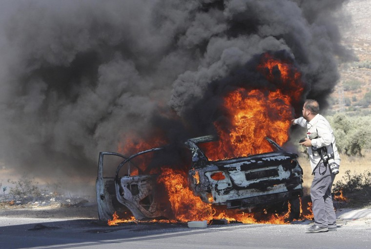 Image: AFP photographer Ishtayeh looks at his burning car after it was hit by tear gas canisters fired by Israeli soldiers, during a protest by Palestinians at Hawara checkpoint near Nablus