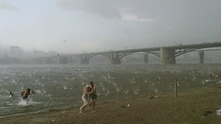 Image: People run to shelter from hailstorm on the beach