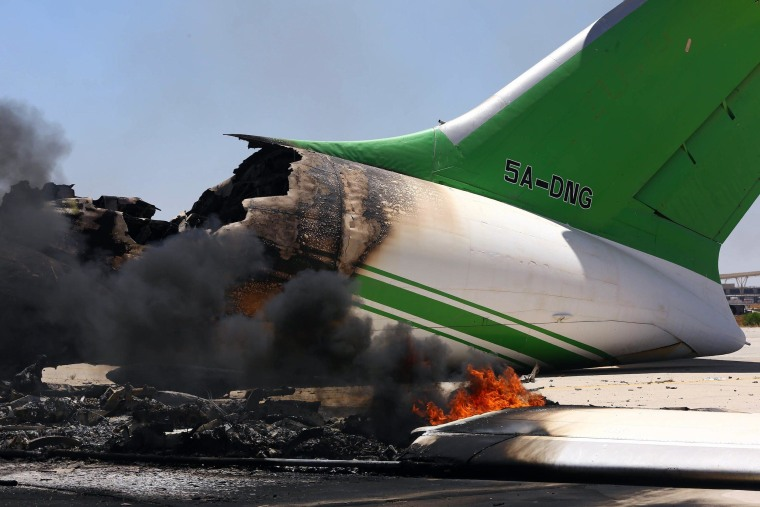 Image: Flames and smoke billowing from an airplane at the Tripoli international airport in the Libyan capital