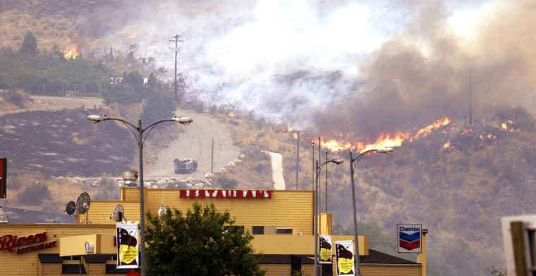 Image: Flames creep down a hillside in view of businesses in Pateros, Wash.