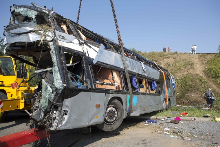 A crashed bus is loaded on a platform at the site of the accident on German A2 highway near the eastern city of Dresden July 19, 2014. A bus from Poland crashed at around 02:00 am into another bus from Ukraine, killing at least nine and injuring some 43 people, local media and German police said.   REUTERS/Axel Schmidt (GERMANY - Tags: DISASTER TRANSPORT TPX IMAGES OF THE DAY)