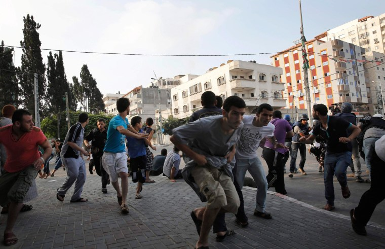 Image: Palestinians take cover as warning Israeli air strikes are fired at a nearby building in Gaza City