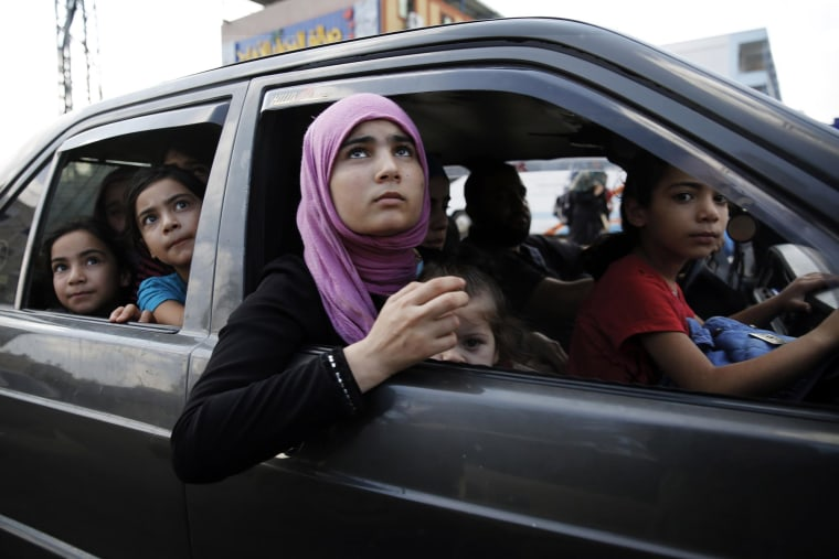 Image: Palestinians flee in a vehicle from Israeli shelling in Bet Lahiya in northern Gaza Strip