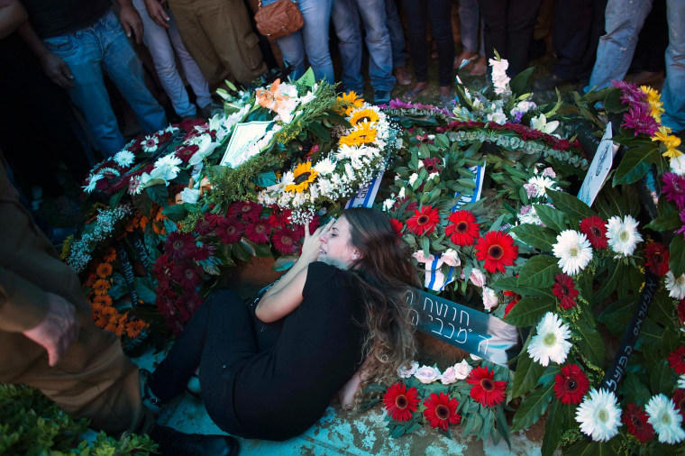 Image: The girlfriend of Israeli soldier Yifrah mourns as she lies atop his grave during his funeral near Tel Aviv