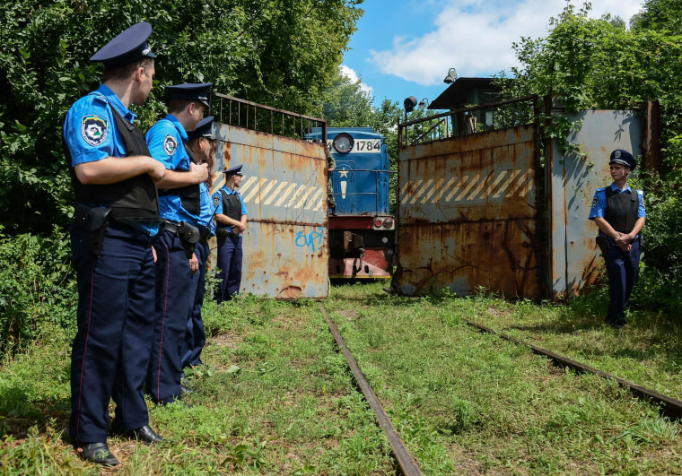 Image: Police officers secure a refrigerated train loaded with bodies of the passengers of Malaysian Airlines flight MH17
