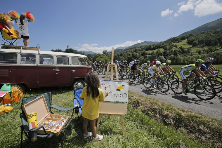 Image: A child makes a painting of cyclists as the pack with Australia's Simon Gerrans passes during the sixteenth stage of the Tour de France cycling race over 147.6 miles with start in Carcassonne and finish in Bagneres-de-Luchon, France, on July 22.