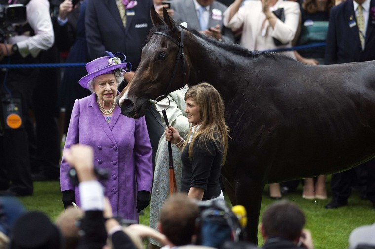 Image: Britain's Queen Elizabeth II stands beside her horse, Estimate, in the winner's enclosure after it won the Gold Cup on the third day of Royal Ascot, in Berkshire, west of London