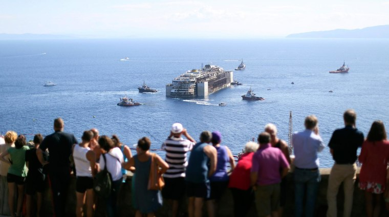 Image: People watch the cruise liner Costa Concordia moving anticlockwise during the refloat operation maneuvers at Giglio Island