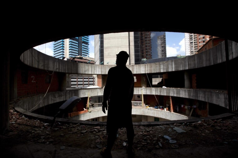 A resident waits for transportation to a new home after being evicted from the world's tallest slum, the Tower of David, a half-built skyscraper that was abandoned in the 1990s and was transformed by squatters into a vertical ghetto, in Caracas, Venezuela, Tuesday, July 22, 2014. Officials and armed soldiers began moving out the first of thousands of squatters who have lived for nearly a decade in a soaring, half-built skyscraper in the heart of Caracas.