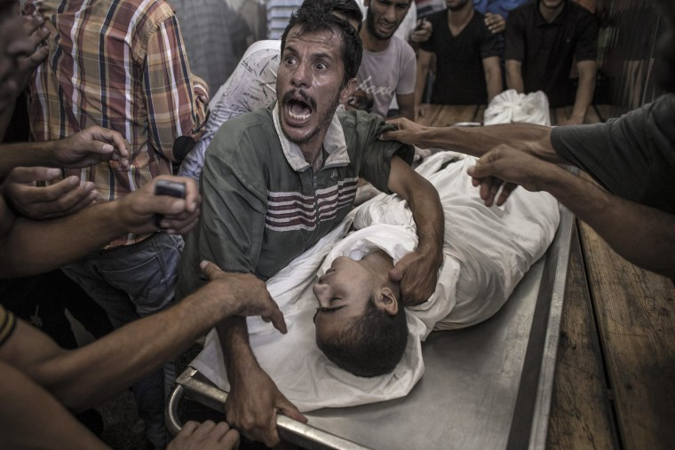 A Palestinian man cries over the body of his son who died when a UN school for refugees was hit by an Israeli tank shell in the Kamal Adwan hospital in Beit Lahiya, Gaza Strip, 24 July 2014.