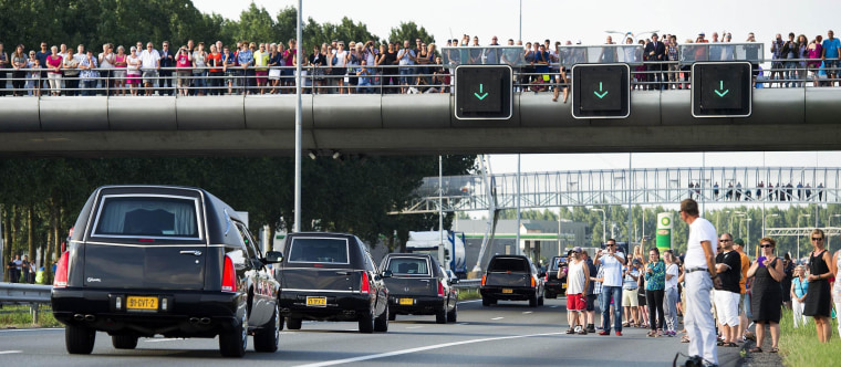 Image: People look as hearses carrying the remains of victims of flight MH17 are escorted on highway A27 near Nieuwegein by military police