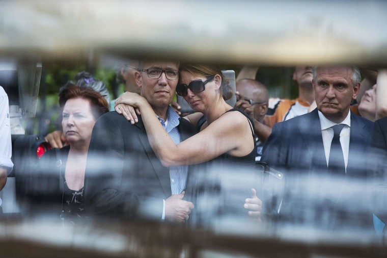 Image: Family members of the victims killed in Malaysia Airlines Flight MH17 plane disaster are seen reacting through the window of a hearse carrying the victims' bodies, as they arrive at the Korporaal van Oudheusden barracks in Hilversum