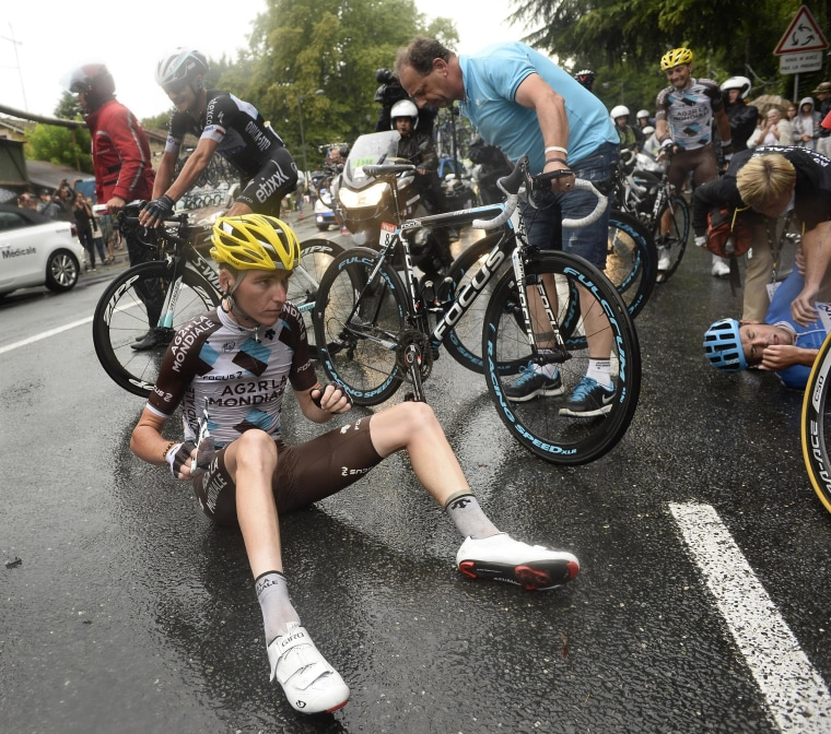 Image: New Zealand's Jack Bauer, right, and France's Romain Bardet left, wait for assistance after crashing in the last two miles of the nineteenth stage of the Tour de France on Friday.
