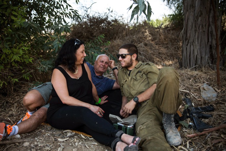 Image: Ruty Friza, left, and Pini Friza, center, meet with their son, First Lieutenant Ziv Friza during a 12-hour ceasefire just outside the militarized zone near the Israeli-Gaza border near Kafar Aza, Israel