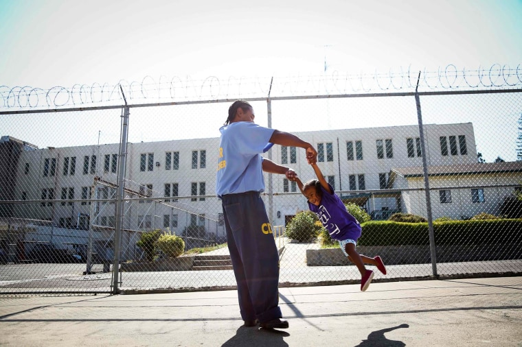"""Image: Pharaoh Haywood plays with his daughter during a \""""Get On the Bus\"""" visiting day to Folsom State Prison"""