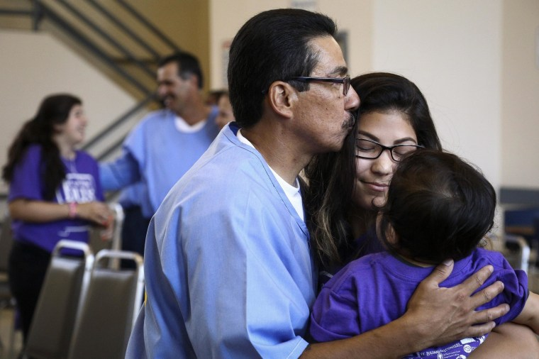 "Image: Manuel Zarate hugs his daughter and grandson at the end of a ""Get On the Bus"" visiting day to Folsom State Prison"