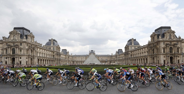 Image: The pack rides past the Louvre Pyramid in Paris