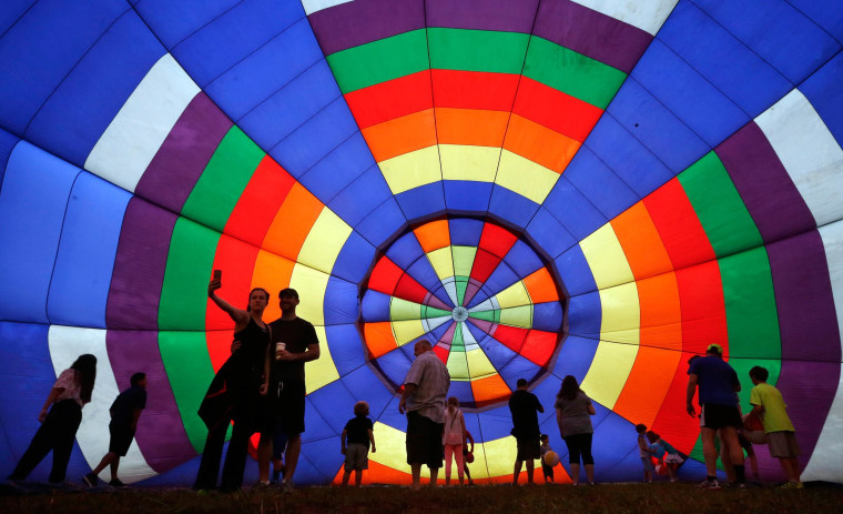 Image: People walk around inside a partially inflated hot air balloon