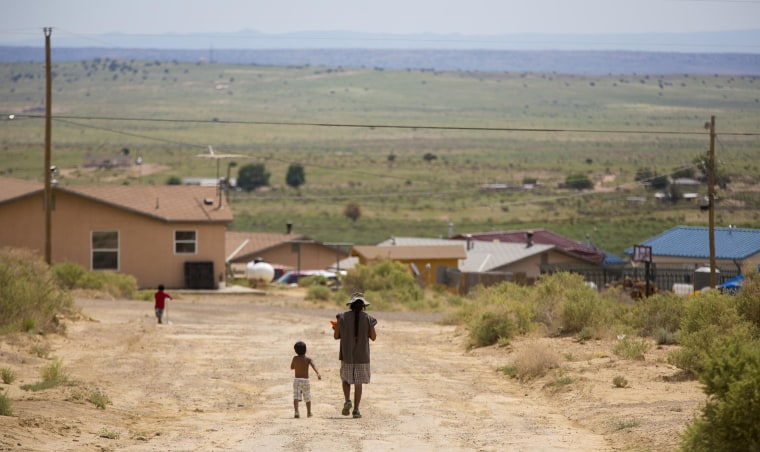 Image: Martin Sando walks along a road in the with his sons after picking up a free lunch at the To'hajiilee reservation.