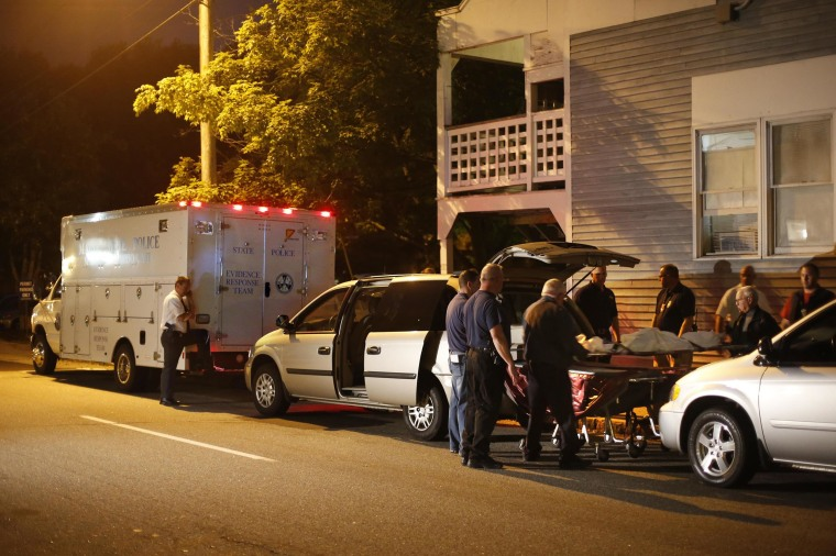 Image: A body is moved from a crime scene at an apartment complex where five members of a family, including three children, were found dead