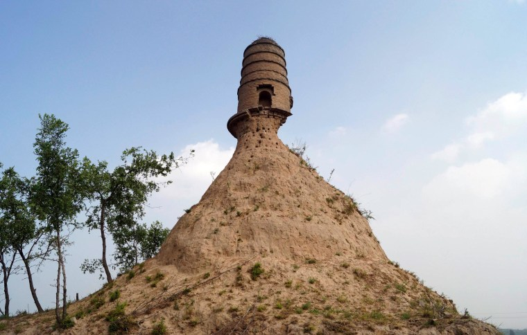 Image: An ancient tower is seen balancing on the top of a dirt hill, with its base slightly eroded, along a grassland in Qixian county