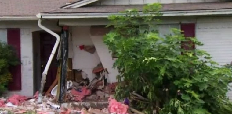 Image: A man has been arrested after police said he became upset and intentionally drove his car into his home early Tuesday morning, trapping his wife in the rubble.